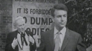 The Doctor and Ian in front of a sign forbidding the dumping of bodies in the river