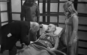 The Doctor tends to the ill Commander.  Beside him is the commanders daughter and a Mark 1  Monoid sans voice box