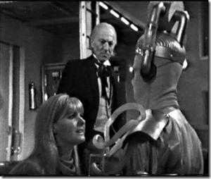 Polly tries unsuccessfully to reason with a Cyberman.  The Doctor looks on