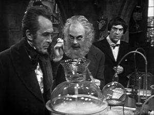 The Doctor looks on as Edward Waterfield and Theodore Maxtible discuss their experiment