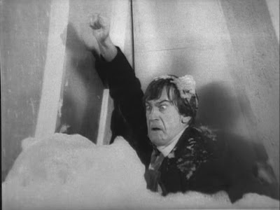 The Doctor is covered in foam as he attempts to gain entry to the Weather Station