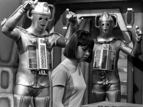The companion-in-waiting, Zoe, with two Cybermen