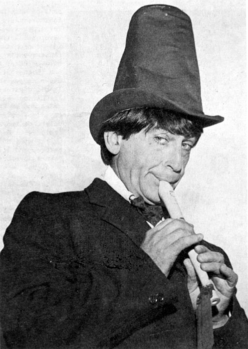 A publicity shot of Patrick Troughton wearing his trademark stove pipe hat and playing a recorder